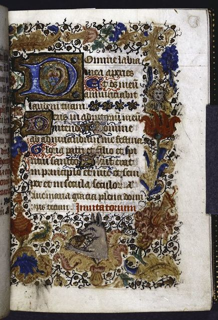 Opening of main text.  Full border with human and animal figures.  Hierarchy of initials, with penwork.  Rubric.