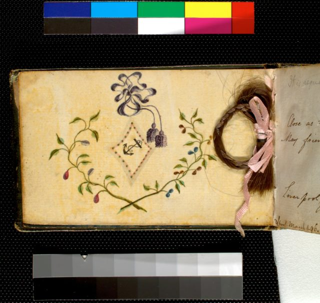 Anchor in a floral frame. (Braided lock of hair enclosed between two pages)