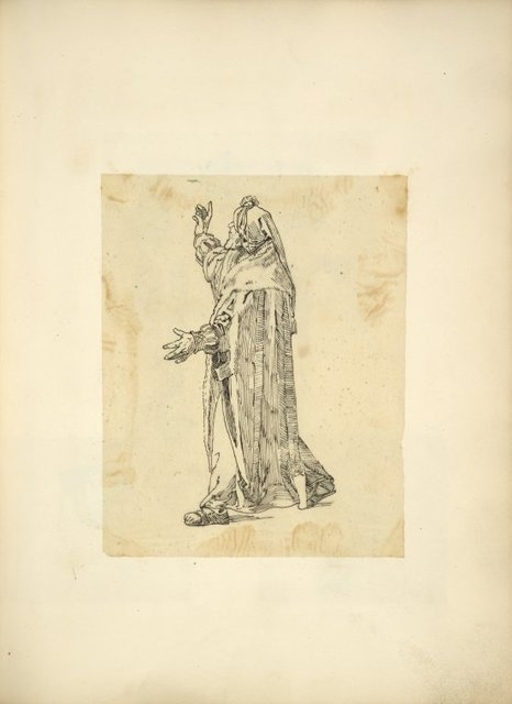 Man in robe and hood, gesturing.