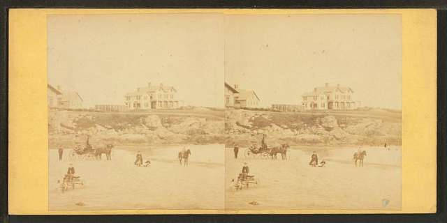 Coaches, horseback rider and people on the beach and houses in the distance.