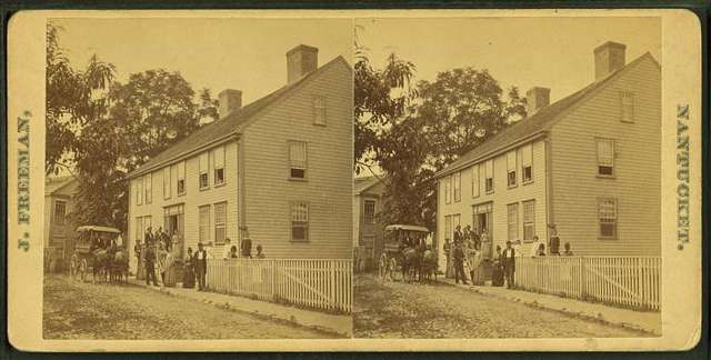 Group posing on porch of large house, possibly a boarding house, with wagonette standing by.