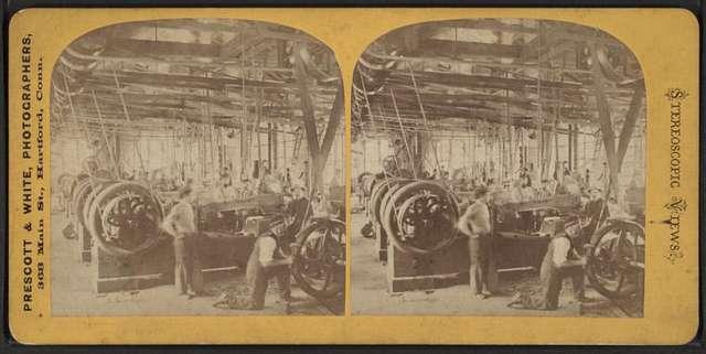 Men in an unidentified mill showing belt driven equipment.