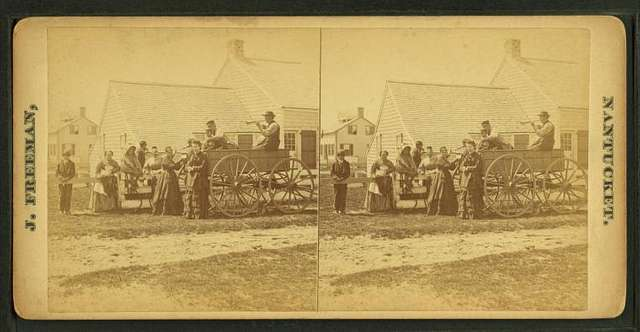 People in and gathered around a wagon.