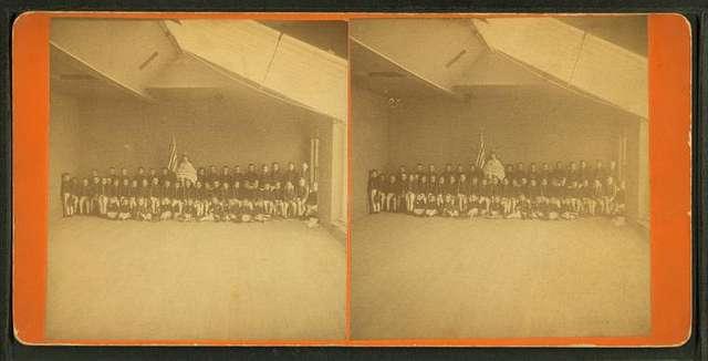 Studio view of 50 children in Revolutionary era outfits.