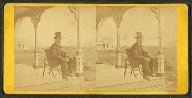 View of a man with a beard and top hat on a porch.