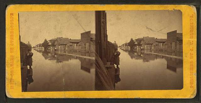 Wooden houses along a flooded Main street.