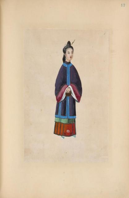 [Woman wearing purple tunic with blue trim and pink cuffs.]