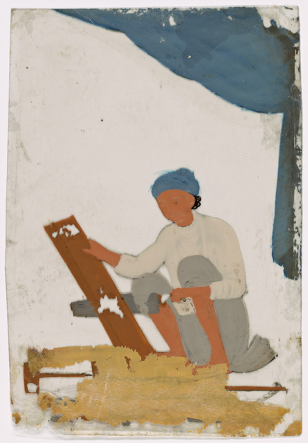 Seated male carpenter sawing a board, with tools on the ground