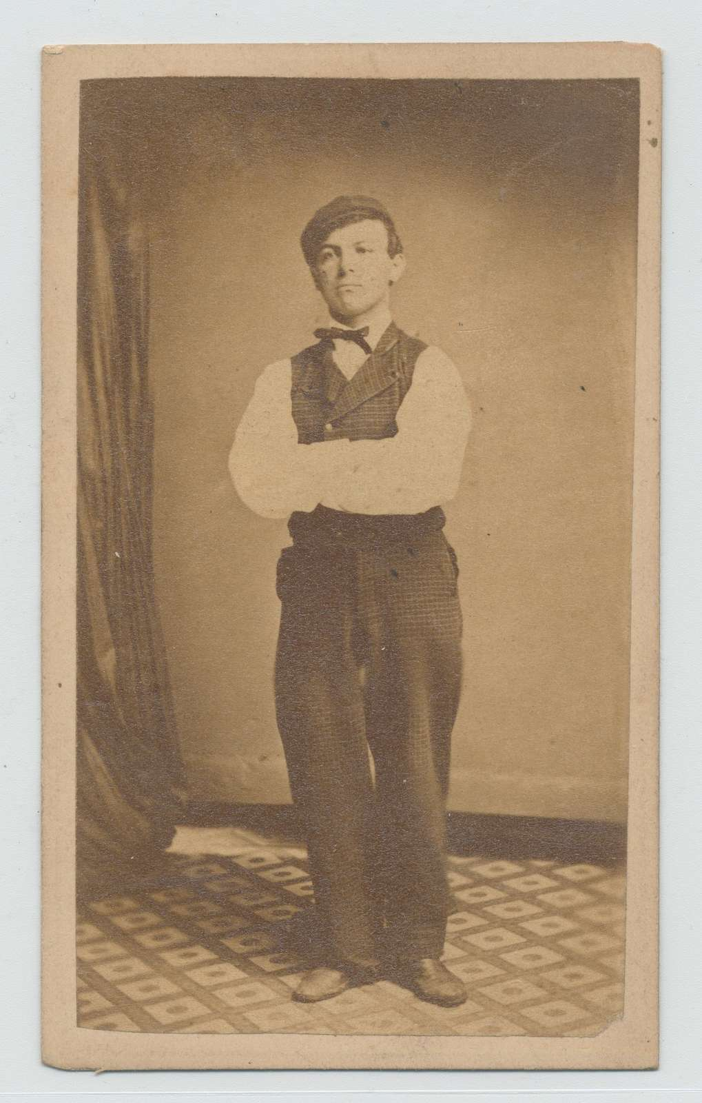 Man with injured right leg stands clothed in shirt, vest and pants, with arms crossed