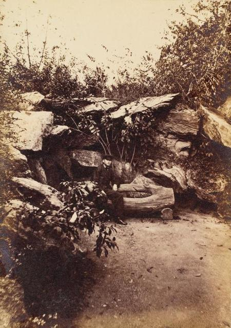 [Man seated on rustic bench in rock grotto.]