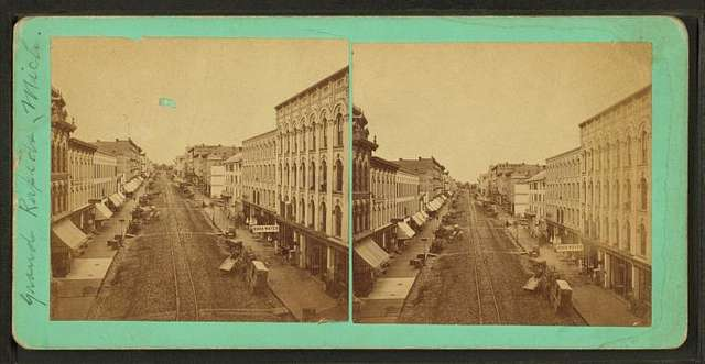 Street scene with buildings, trolley tracks, store fronts, and carriages.