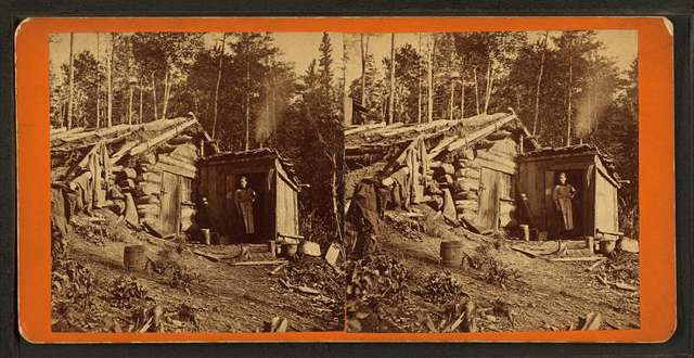 Woman stands in doorway of log cabin on the Northern Pacific Road.