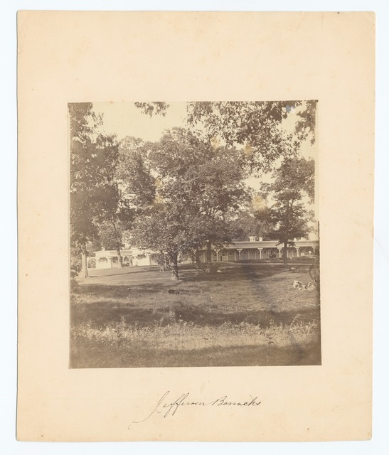Jefferson Barracks [Two long wooden single-story buildings, large trees on lawn in foreground.]