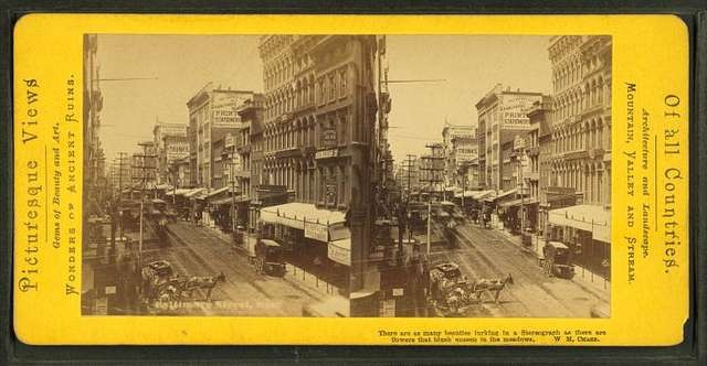 Baltimore street[Street view showing wagons, street car tracks, businesses, signs, awnings].