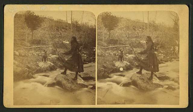Mocassin Bill's daughter [woman wearing short buckskin dress and sword and holding rifle standing on a rock in a creek or river, dog waiting on bank.]
