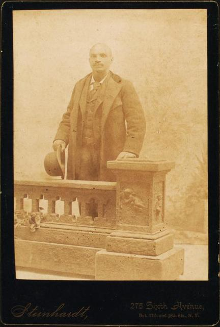 [Studio portrait of man dressed in suit and coat, holding bowler hat.]
