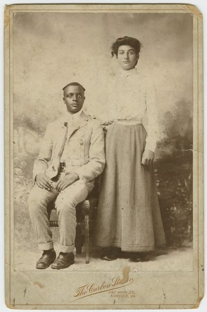 [Studio portrait of a young couple, he seated, she with hand on his shoulder.]