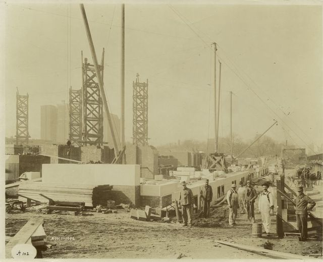 [Exterior marble work : construction workers standing near the northeast corner.]