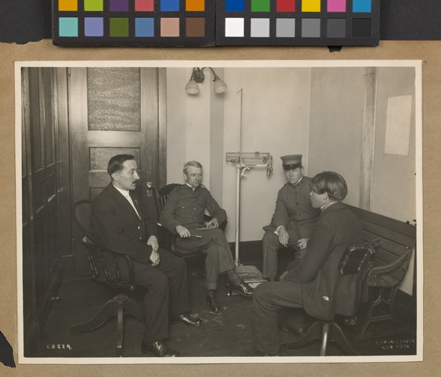 A private interview between a young immigrant and an Ellis Island official. Two staff members [?] are also present.