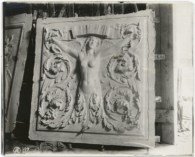 [Plaster model of a panel decorated with a winged nude female figure and leaves.]