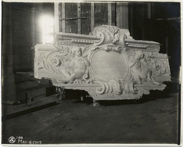 [Plaster model of a panel decorated with two cherubs and foliage.]