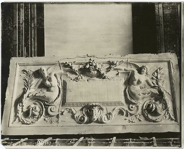 [Plaster model of a panel decorated with winged female figures, fruit, foliage, and a satyr's head.]