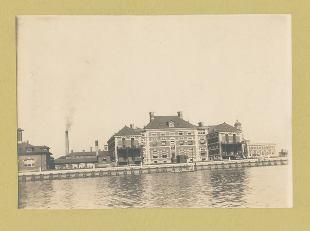 Another view of Ellis Island from the harbor, showing various buildings.