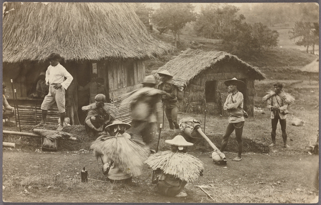 Group of individuals, some wearing thatched rain capes, in front of nipa huts.