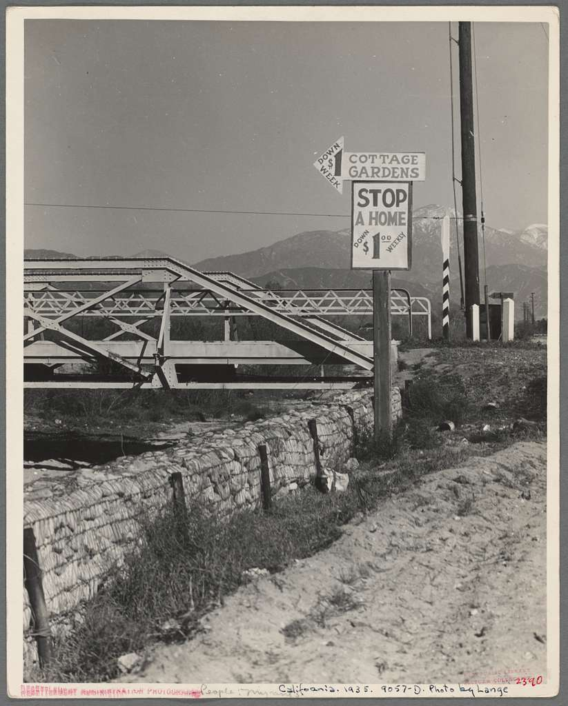 Outskirts of San Bernardino, California. Cottage Gardens road sign. This sign advertises a depression community. There are one hundred homes. All but fifteen of the families were living on SSRA work and buying their homes on this budget ...