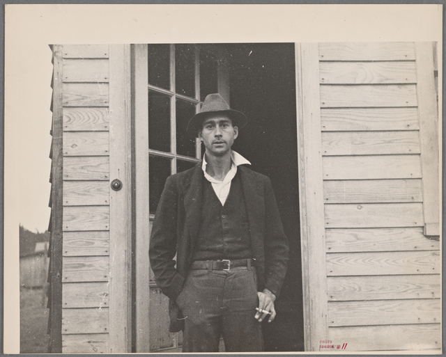 Man with cigarette in a doorway.