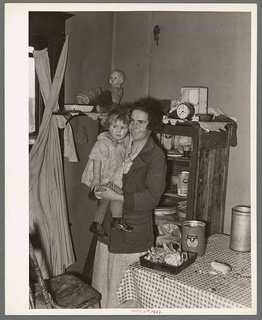 Mother and child in corner of farm home, Sheridan County, Montana