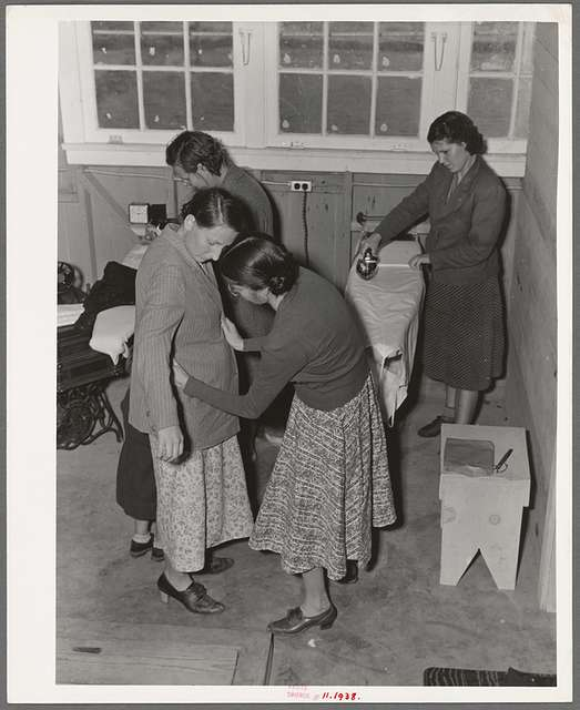 Camper receives help in fitting a coat from Works Progress Administration (WPA) sewing instructor. Shafter camp for migratory agricultural workers (Farm Security Administration-FSA), California