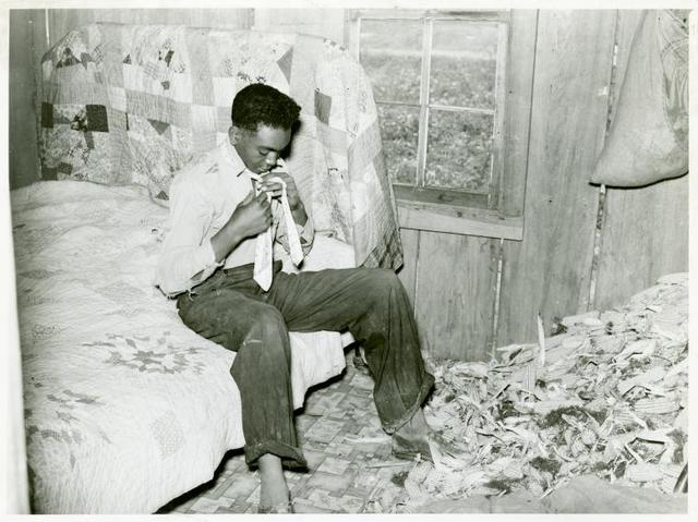 Southeast Missouri Farms. Son of a sharecropper dressing in a combination of bedroom and corn crib, 1938.