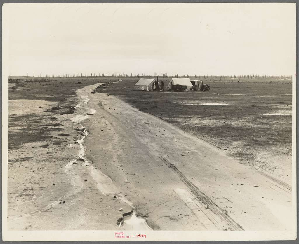 Kern County, California. Camp of two related families seen from U.S. 99. Oil field beyond. Came to California in 1920 from Missouri. Father had job for eight years. Was gang foreman on Los Angeles Aqueduct; laid off two months ago