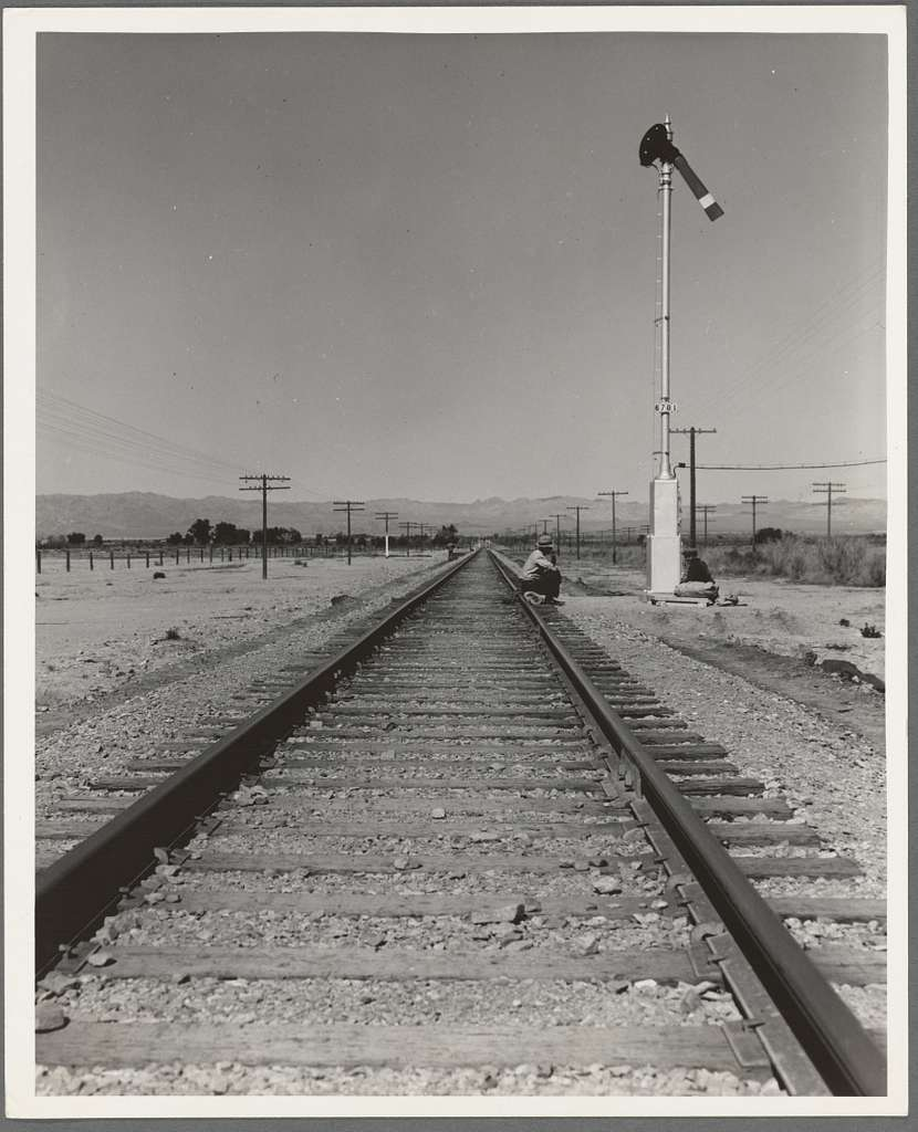 "Looking east down the railroad track, near Calipatria, California. Single men, itinerants with ""bindles"" waiting for the freight"