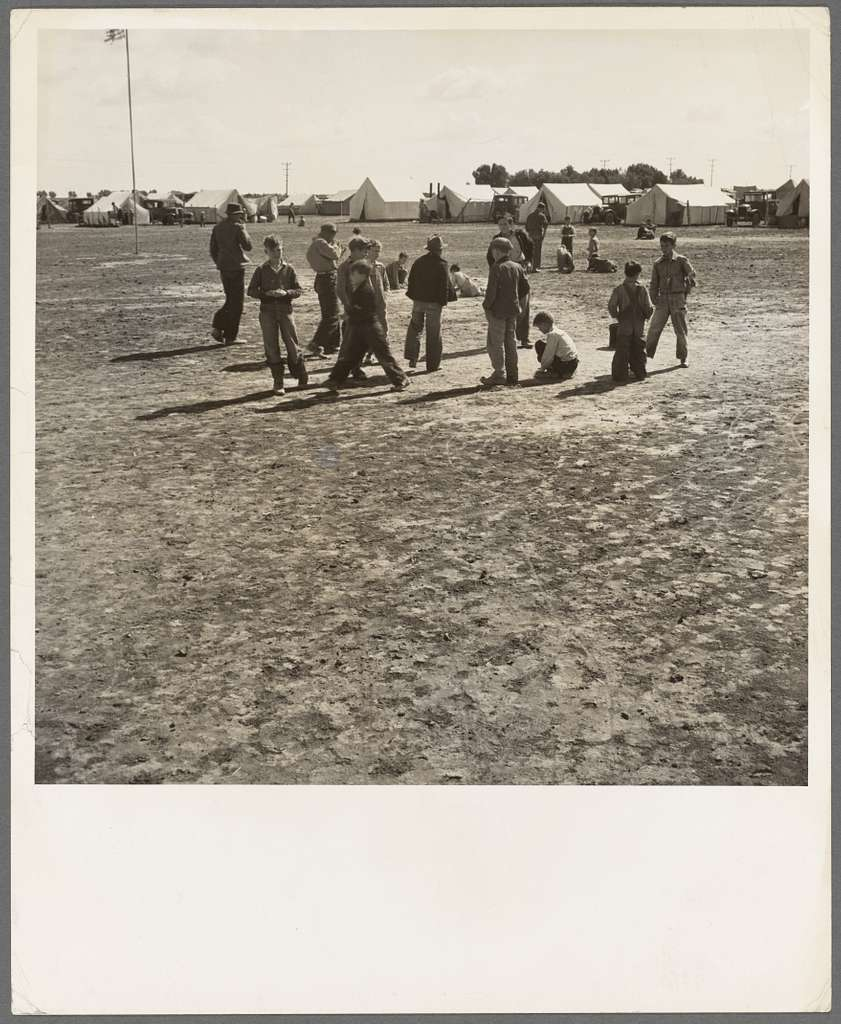 Marble time in Farm Security Administration (FSA) migratory labor camp (emergency.) Plenty of space to play and plenty of companions for the children during pea harvest. Near Calipatria, Imperial Valley, California