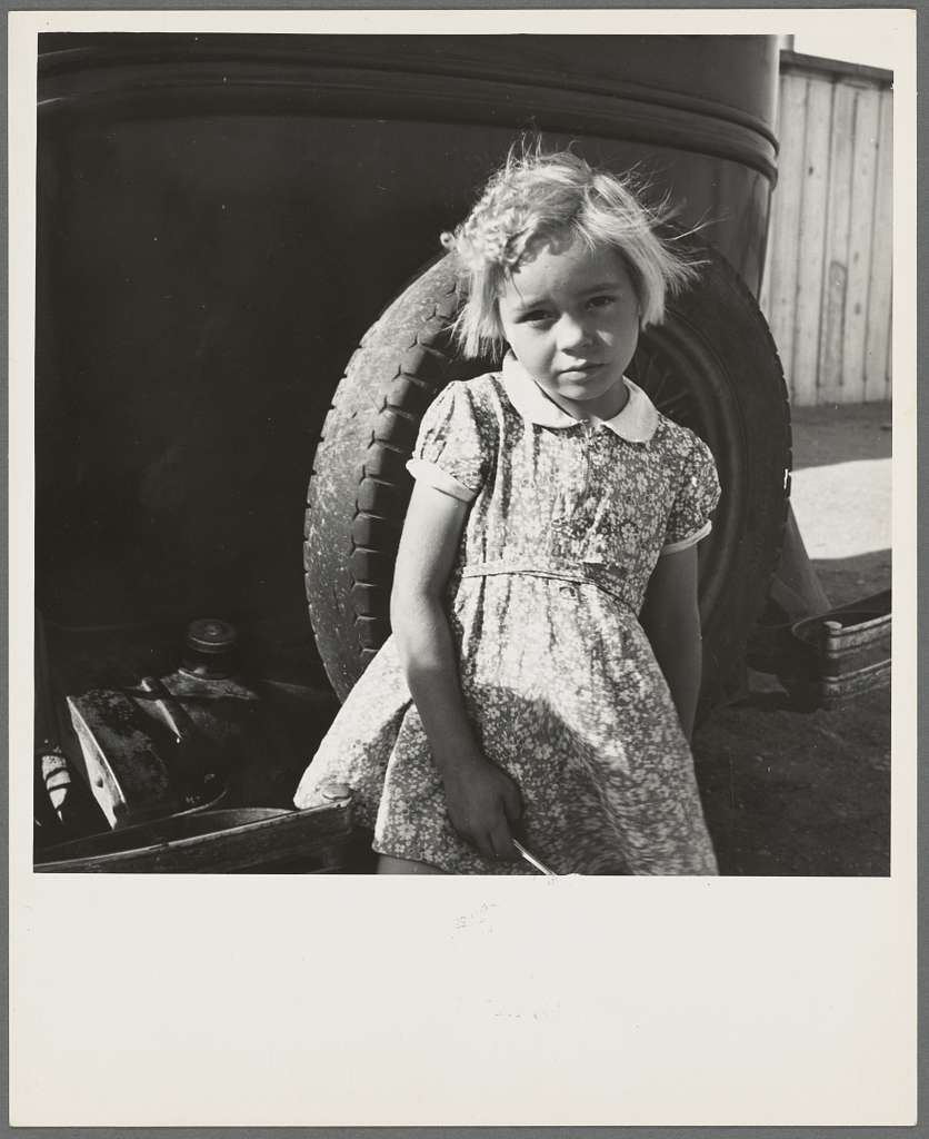 Arkansas girl in migrant camp near Greenfield, Salinas Valley, California. This is an Arkansawyers auto camp, filled almost completely with Arkansawyers recently in California. Rent ten dollars per month for one room, iron bed, electric light