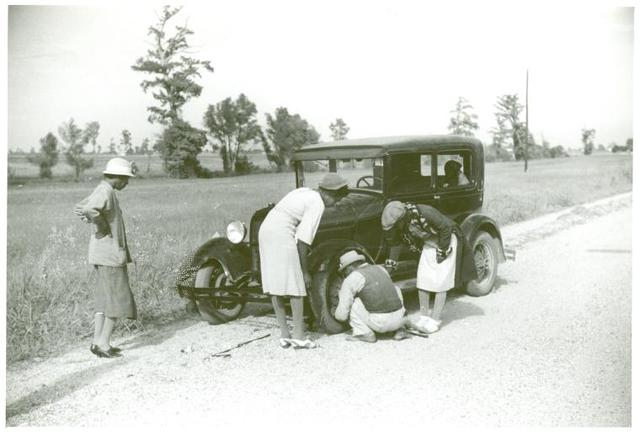 Repairing tire on road near Knowlton Plantation, Perthshire, Mississippi Delta, Mississippi, October 1939.