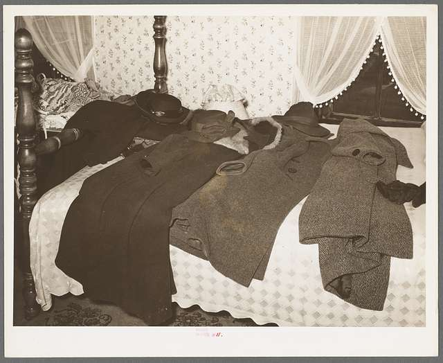 Coats of members of home demonstration club on bed during a meeting. McIntosh County, Oklahoma