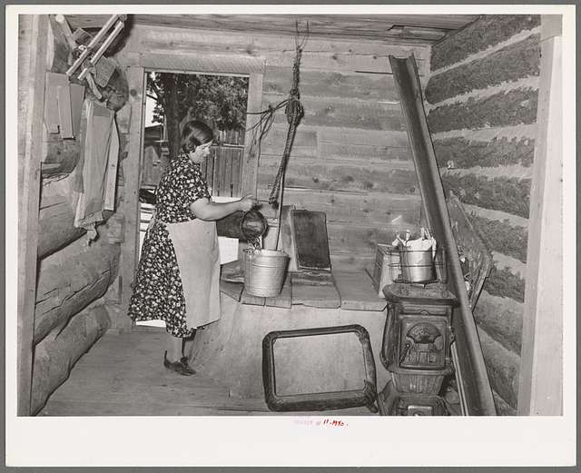 Mrs. Bill Stagg drawing water from her well, which is in enclosed porch in her log house. Pie Town, New Mexico