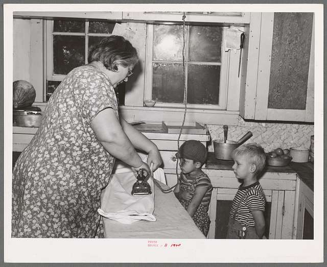 Mrs. J. Webster ironing while her sons look on. Tehama County, California