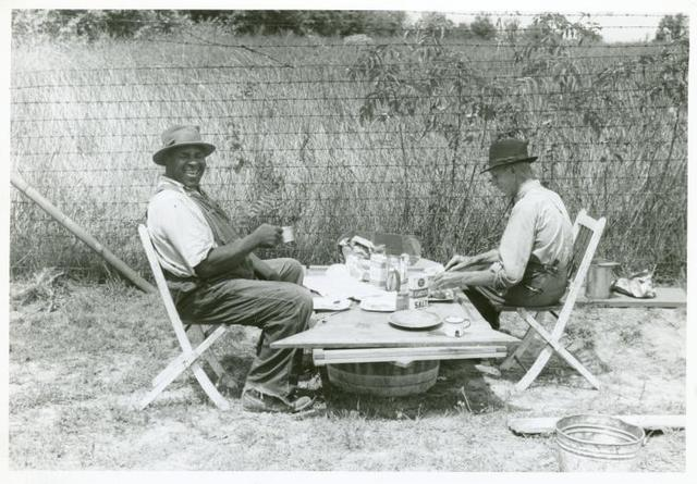 Stable hand and trainer eating picnic lunch before the Shelby County Horse Show and Fair, Shelbyville, Kentucky. Aug. 1940.