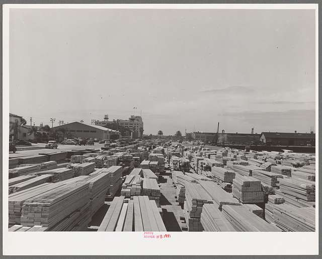 Lumber for construction work stacked in the open along Pacific Highway. San Diego, California