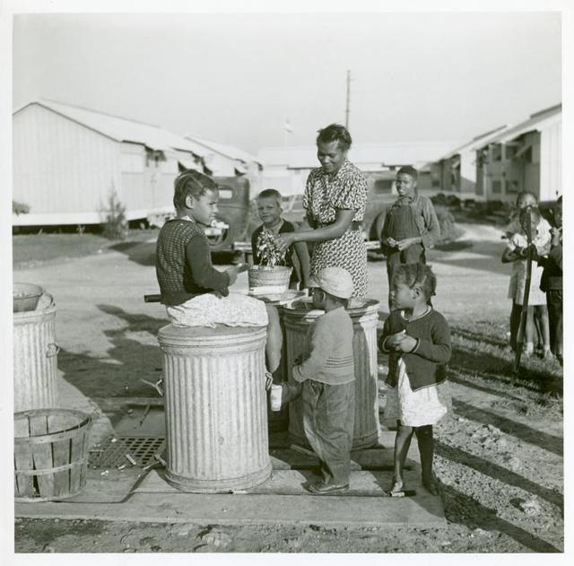 Washing greens by pump near metal shelters at Okeechobee Migratory Labor Camp. Belle Glade, Fla. Feb. 1941