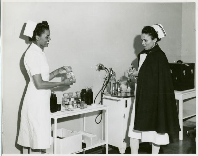 Captain Mary L. Petty, Chief Nurse, holding a glass bottle and showing it to 2nd Lieutenant Olive Bishop, who is writing on a small pad of paper, Fort Huachuca, Arizona.