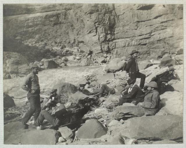A Noonday Rest in Marble Canyon, showing well the head of a fall. Snapshot by James Hogue, 1890. From left to right, Travers (standing), Hislop, Kane, Gibson, Ballard, Edwards, Twining (standing), Stanton, McDonald, Brown.