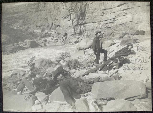 [A Noonday Rest in Marble Canyon, showing well the head of a fall. Snapshot by James Hogue, 1890. From left to right, Travers (standing), Hislop, Kane, Gibson, Ballard, Edwards, Twining (standing), Stanton, McDonald, Brown.]