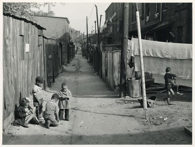 Children playing in the Defrees Alley, NE Washington, D.C.; Near Capitol Building; One basement room rents for $9.00 a month, two rooms upstairs for $ 16.00, one bath and cold water in the hall for entire building.