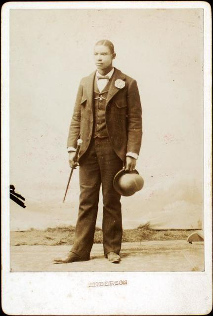 [Full length portrait of man with bowler hat and cane.]