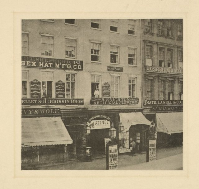 The Broadway Theatre, with posters announcing Julia Dean in The woman in white. Site 485 Broadway. Signboards of H. F. Shepher (Essex Hat M'f'g Co.) at 483, H. Knighton and Alfred Plunkett at 485, Lasell & Co. (hats) at 487.